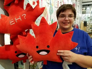 """A maple leaf pillow with """"Eh?"""" embroidered on the back at Quilts Etc. elsewhere in the mall."""
