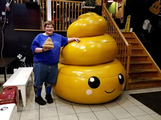Elyse poses with a giant poop located near the entrance, and holds a stuffed poop alongside it.