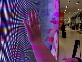 Elyse puts her hand on a light wall in the store.