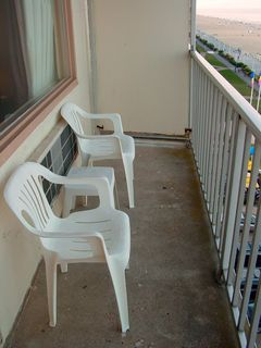 The balcony was a simple affair, with a concrete floor, a railing, and the retrofitted-in sides. The furniture was basically the same as at the Ocean Holiday. Two chairs, and a little table.
