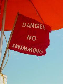 """The red flags were out on this particular day. Some of the flags were straight red, while some were printed with """"DANGER NO SWIMMING""""."""