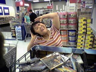 Becky is making funny faces in front of the big DVD bin...
