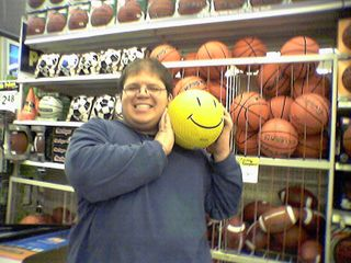 """Back in Sporting Goods, Becky took a shot of me holding what I described as """"the quintessential Wal-Mart item"""", a yellow playground ball with the Wal-Mart happy face on it."""