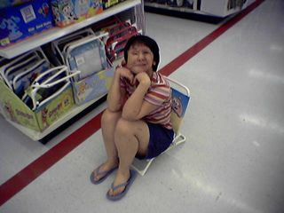 Becky takes a break during our shopping trip, alighting on this fold-up chair.  I think the chair's just a wee bit too short, but otherwise, pretty good.