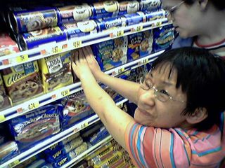 Becky tries unsuccessfully to get a package of cookie dough back on the shelf.  Turns out there was a barrier on there that she was missing.