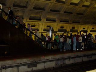 People take the escalator to cross over to the Shady Grove platform in order to catch their Glenmont-bound train.
