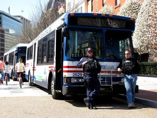 Police officers stand next to a Metrobus, waiting to pick up any arrestees for the civil disobedience action planned for later.
