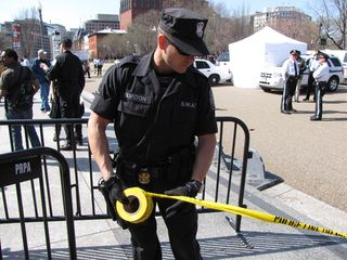 A SWAT officer cordons off an area of Pennsylvania Avenue with police tape.