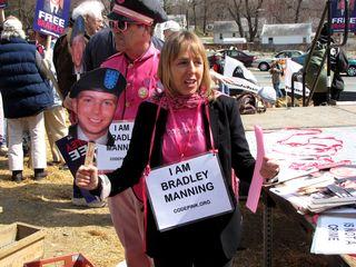"""Medea Benjamin holds up Bradley Manning masks and """"I AM BRADLEY MANNING"""" signs."""