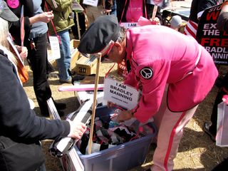 Another Code Pink volunteer hands out prison-striped costumes, and chains to go with the costume.