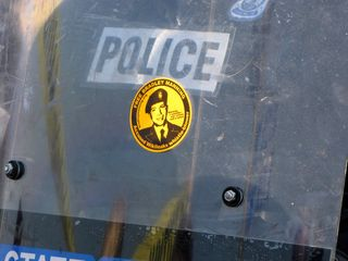 """State Police in riot gear, with """"Free Bradley Manning"""" stickers on their shields."""