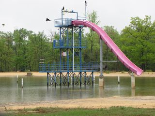 The tower at Shenandoah Acres in Stuarts Draft, in its final incarnation as home of the Pink Zipper slide, seen here on May 3. The end of the slide normally would be closer to the water, but the lake's water level was lower than where it would normally be when the facility was still in operation (Shenandoah Acres closed in 2004). This tower previously held a cable ride, where guests would hold onto handlebars and slide down a long cable from the uppermost level. This is likely one of the last pictures of the tower ever taken, because the tower was demolished later that year.