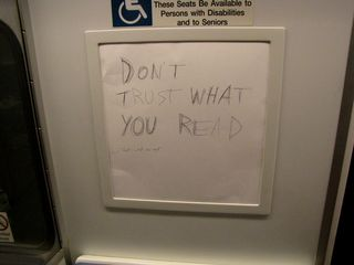 """On the Metro coming back from the impromptu raid, we spotted this in one of the ad boxes on Breda 3119. Someone had taken the advertisement that was in there, flipped it around, and wrote """"DON'T TRUST WHAT YOU READ"""" in big letters on it. The smaller text says, """"That's what she said."""""""