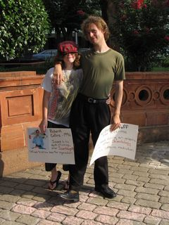 Hunter poses with his girlfriend, both holding signs remembering victims of Scientology.