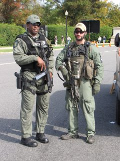On October 25, while waiting to meet up with Isis and Cubby to photograph in Arlington Cemetery, I got to observe some of the 2009 Marine Corps Marathon in progress. These two law enforcement officers, representing Arlington County (left) and the FBI (right), were a bit over the top. Are the big guns really necessary for this sort of event? Really?