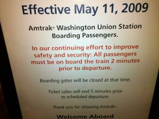 """While checking our bags at Union Station in DC, I noticed this sign. This annoyed me because Amtrak is throwing """"safety and security"""" around when this is obviously neither a safety nor a security issue. Let's be honest here: All passengers need to be on board the train two minutes prior to departure so that the train can depart on time. It is a very important concern, but not a matter of safety and security to keep a schedule, unless the passengers will be revolting and subsequently offing the conductor if the train doesn't leave on time. Keeping the schedule is important because if you're delayed leaving one stop, all the subsequent stops will be delayed as well, and that's no way to run a railroad..."""