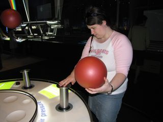 Sis explores how the floating ball device works. Normally, the ball that she is holding in her one hand hovers over the tube that she is touching with her other hand.