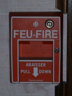 "Two things you always take for granted - exit signs and fire alarms. In a country with two official languages (English and French), everything was bilingual. Thus ""SORTIE"" is added to an exit sign, and ""FEU"" is added to a fire alarm pull station."