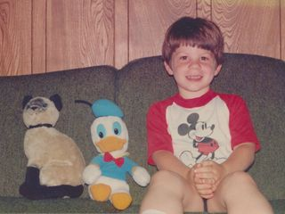 "This was a recurring scenario in my childhood: posing for photos with stuffed animals. In the left photo, I'm sitting on the couch with a stuffed cat we called ""Smoky"" (there was a similar cat in the Children's Department on the early seasons of Today's Special, by the way), and Donald Duck. Then in the right photo, I'm posing with E.T. and a Glo Worm."