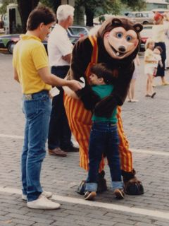 At another event in downtown Rogers, I'm getting a hug from Billy Bob (of Showbiz Pizza fame), while a man tries to hand me a flier of some sort. I love my expression here, kind of saying, do you mind?