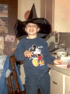 Posing in my Mickey Mouse sweatshirt while wearing a witch's hat, in October 1987. Note the missing tooth that I am sporting in the photo.