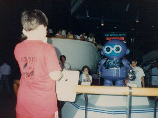 Near Spaceship Earth, at the CommuniCore attraction (which no longer exists), a I take my turn interacting with the robot seen in the distance, using a telephone handset.
