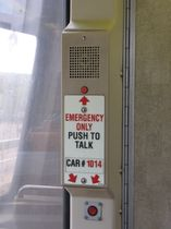 Emergency intercom: Emergency intercoms on 1000-Series cars are tan in color, have two call buttons, and have large glow-in-the-dark signage.