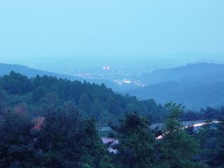 From the mountain above in the early evening, the lights of the nearby city of Waynesboro seem very distant through a slight haze, even though the city is only a few miles away both north and west of Afton Mountain.