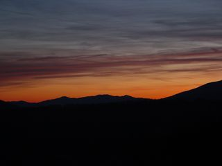 About three miles east of the motel buildings on Afton Mountain, at a scenic overlook on Interstate 64, the sun sets over a partly cloudy sky...