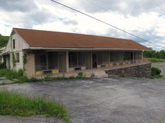 Abandoned motel rooms above the old tourist information center. Note the hole in the roof.
