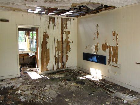 Abandoned motel room showing extensive damage.
