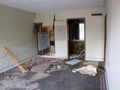 Abandoned motel room with a large section of wallboard missing.