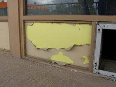 Peeling paint on the exterior of the abandoned motel rooms, showing the original yellow color.