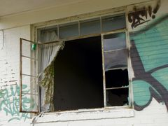 A curtain blows in the wind in one of the abandoned guest rooms.