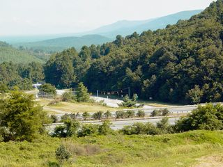 Afton Mountain is part of the Blue Ridge Mountains, with traffic crossing Rockfish Gap via Interstate 64 (top left), and US 250 (lower left), with views of Waynesboro (top right) and Nelson and Albemarle Counties (lower right).