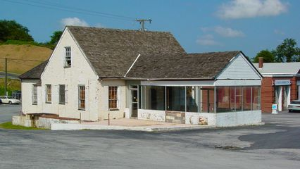 A building that once housed a gift shop and motel office sat in front of the Skyline Parkway Motel's cabins. This motel appeared to have undergone a number of modifications since it first opened, as the front section (glassed in) of the gift shop did not appear in postcards, and a number of the buildings looked considerably different than the postcards indicated.