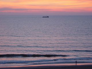 And as the sun rises higher and the sky reflects a pinkish hue, boats sail some distance offshore.