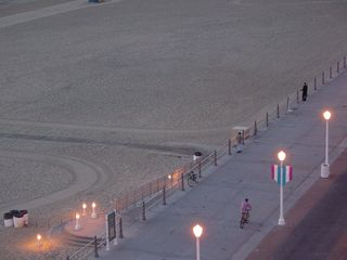And along the boardwalk, people are walking and riding bicycles, while the artificial lighting still glows brightly.