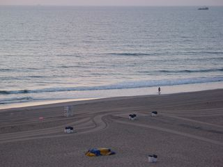 The crews out smoothing the sand have made some progress, having made a few lines up and down the beach.