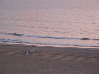 All the while, people watch the sunrise from the lifeguard's chair, and the waves continue to break along the beach.
