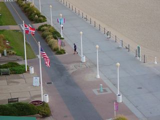 The lampposts are now completely out along the boardwalk, as a pedestrian walks past Norwegian Lady Plaza.