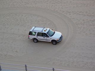 A Public Works vehicle travels across the beach, cutting a swath across a loop that the sand-smoother left behind.