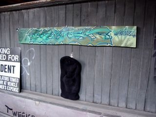 Near the top of the stairs, a small panel with graffiti on it hung above a paint-spattered ski mask, presumably worn while graffiti artists do their thing.