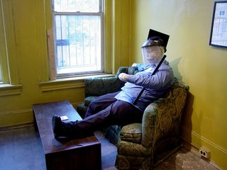 The mannequin of the police officer depicts police in an unfavorable light, showing a somewhat-overweight officer sitting on a couch watching TV, with one foot on the coffee table, nightstick tucked under one arm, shirt untucked, and wearing a riot shield and graduation cap.
