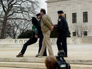 When I first arrived, two people were engaging in civil disobedience. It was stated by law enforcement officers on site to stay on the sidewalk, and not to go onto the steps. When these individuals stepped off the sidewalk and onto the Supreme Court's patio, law enforcement took notice. Pete Perry, wearing the brown jacket, was detained briefly and released (the officer is merely holding his hands behind his back), while Midge Potts, wearing a green shirt and an Abu Ghraib hood, was handcuffed and arrested.