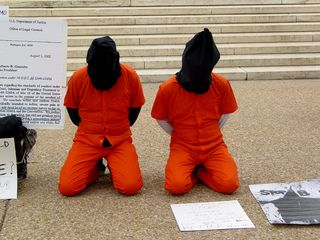 The main theme of the demonstration was to show victims of torture, with Guantanamo Bay and Abu Ghraib featured prominently. Participants held their hands behind their back as if handcuffed or otherwise restrained.