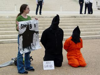 """Some participants had signs near them, such as """"Abu Ghraib"""" and """"Guantanamo Bay""""."""