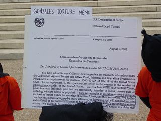"""On a sign labeled """"Gonzales Torture Memo"""" is an enlarged version of the first page of a memorandum for Alberto Gonzales, dated August 1, 2002, regarding """"Standards of Conduct for Interrogation under 18 U.S.C. §§ 2340-2340A""""."""