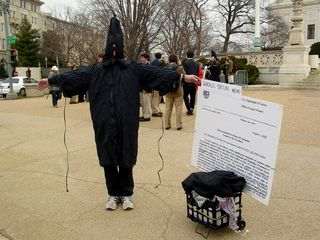 A man poses in a manner similar to a famous photo run by news organizations in order to remind those passing by of torture tactics used by our own military personnel.