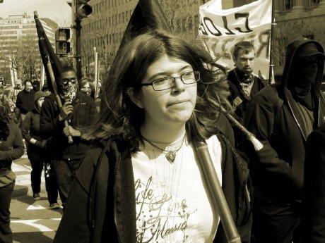 A woman carries a black flag during a radical feeder march